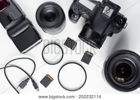 Modern Photo Camera, Lenses And Equipment Over White Table Background