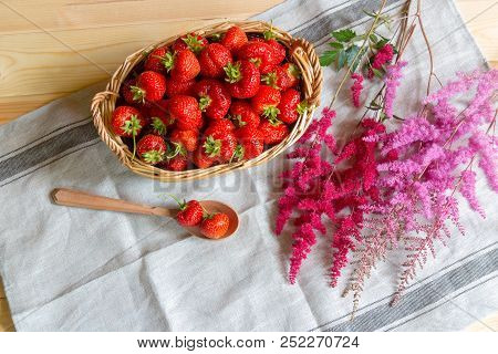 Ripe Red Strawberries In Basket And Astilbe Flowers On  Table. Top View.