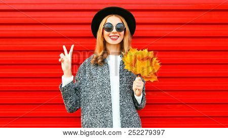 Happy Pretty Autumn Cool Girl With Yellow Maple Leaves On A Red Background