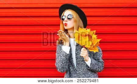 Elegant Autumn Pretty Woman Sends An Air Kiss With Yellow Maple Leaves, Wearing Coat On Red Backgrou