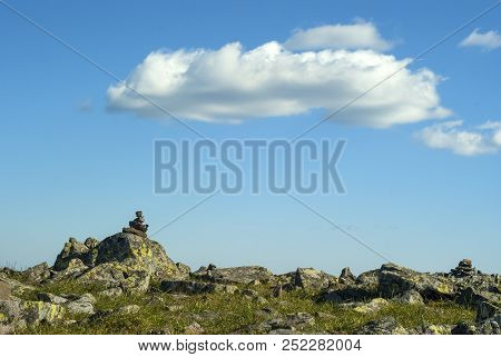 Rocky Grassy Terrain On A Mountain Pass And A Blue Sky With Clouds Above It