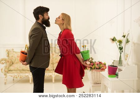 Couple Concept. Couple In Love Celebrate Spring. Couple Of Man And Woman Hide Flowers Behind Their B