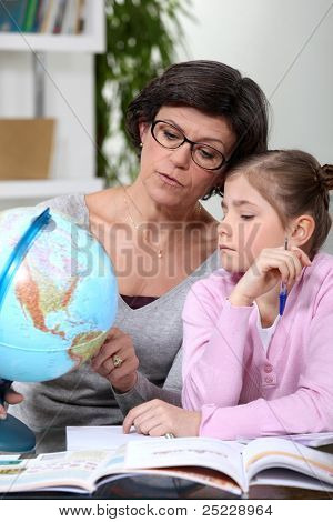 mother holding a globe and giving explanations to her daughter
