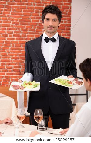 Waiter delivering meals to table