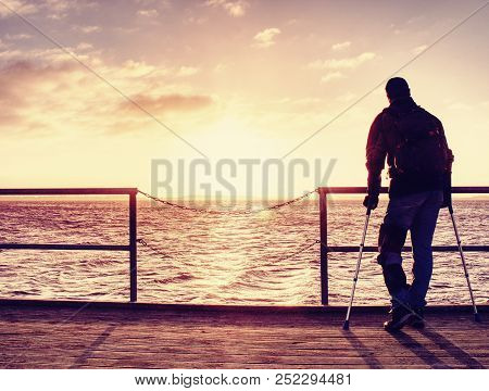 Hurt man with hooded jacket and forearm crutches  standing on sea bridge within  early morning and thinking. Gloomy nostalgic silhouette of sad lonely melancholic adult. poster