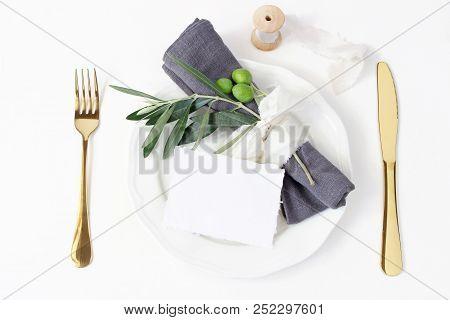 Festive Table Summer Setting. Golden Cutlery, Olive Branch, Linen Napkin, Porcelain Dinner Plate And