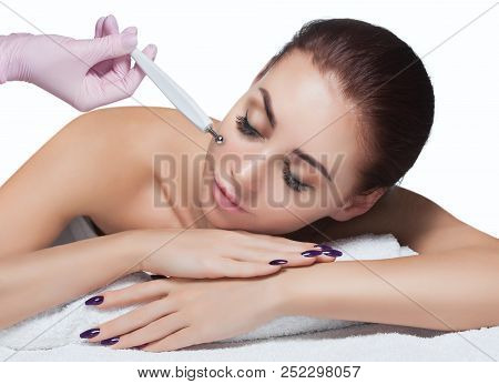 The cosmetologist makes the apparatus a procedure of Microcurrent therapy of a beautiful, young woman in a beauty salon. Cosmetology and professional skin care. poster