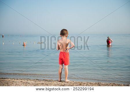Pensive Little Kid In Shorts Standing On Summer Beach