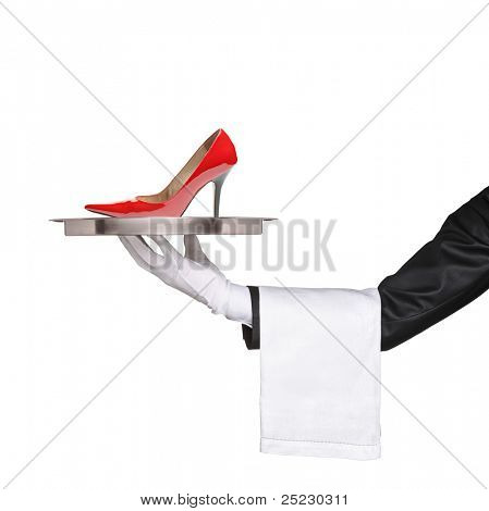 A waiter holding a silver tray with a red high heel on it isolated on white background