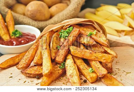 Homemade Crispy Seasoned French Fries. French Fries  With Spicy Seasoning In Brown Paper Bag On Wood