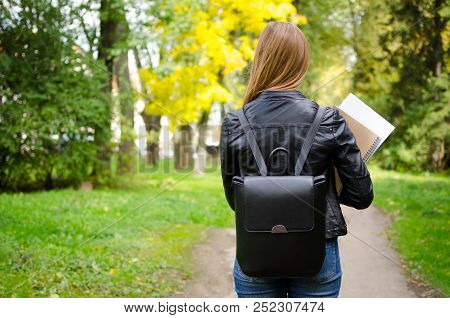 Rear View Of Young Adult High School Or College Student Girl Walking In The Park On Her Way To Class