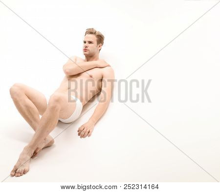 Sexy Man In Underwear. Muscular Male Model In Trendy White Underwear. Handsome Sexy Naked Man Lying