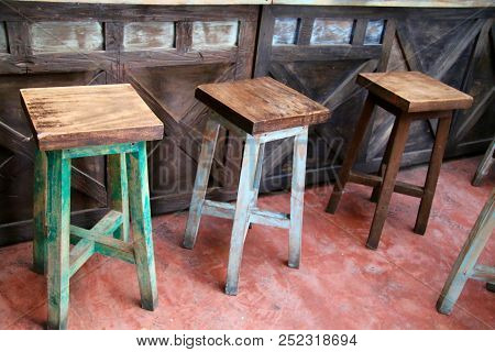 Three Wooden Stools Next To A Wooden Bar