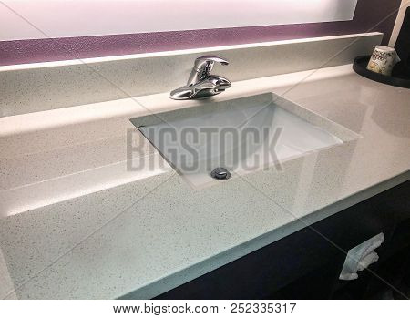hotel quartz counter top. backsplash and counter made of quartz countertop. rectangular sink on quartz counter. white sink and faucet installed in quartz countertops. quartz made from natural stone