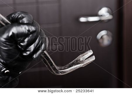Burglar Hand Holding Crowbar Break Opening Door