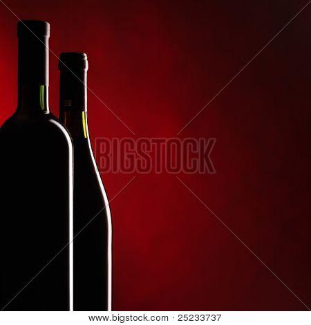 Garrafa e copo de vinho tinto em fundo vermelho escuro