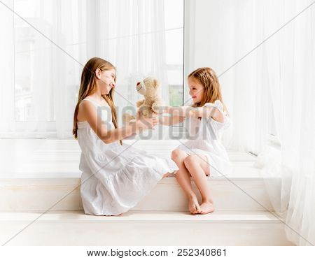 Little girl giving her teddy bear toy to older sister. Cute child girl giving a gift for her sister. Child girl sharing toy with friend