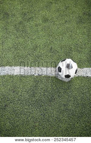 View of leather soccer ball on white line dividing field for play in two parts