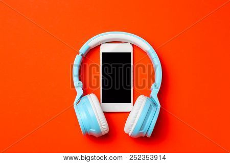 Blue Modern Wireless Headphones With A Mobile Phone On Red Orange Background. Listening To Music Con