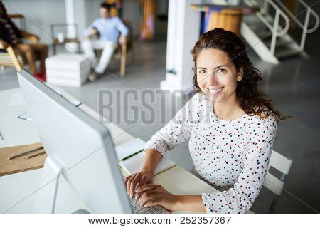 Cheerful office manager with toothy smile sitting in front of computer monitor and networking