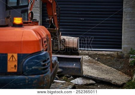 Digger ( Partly Out Of Focus ) In Front Of Black Dirty Garage At Concrete Yard Construction