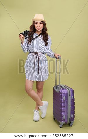 Pretty Young Traveler With Digital Camera Leaning On Her Suitcase And Smilng At Camera