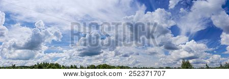 Wide Panorama Of The Sky With Cirrus And Cumulus Clouds Over A Flat Terrain Covered With Forest At S