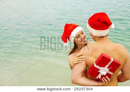 Portrait of happy female in Santa cap embracing her husband while he hiding gift behind his back