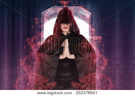 Attractive Witch Woman Showing Her Magic Power With Wall Background