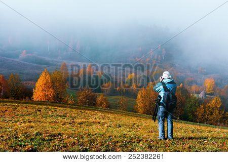 Photographer taking photo of autumn landscape with foggy peaks and orange trees. Ukrainian Carpathians mountains