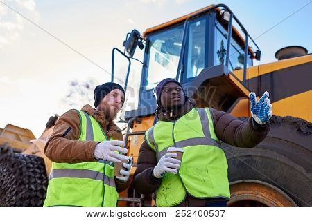 Low Angle Portrait Of Two Workers, One African-american, Drinking Coffee And Chatting Standing Next