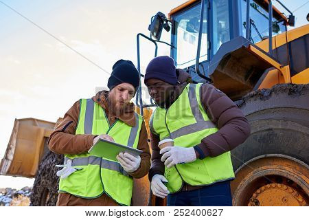 Waist Up Portrait Of Two Industrial Workers, One African-american, Drinking Coffee And Using Digital