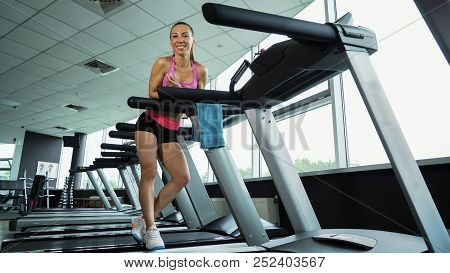 Young Smiling Woman Relaxing On Treadmill In Fitness Club, Gym And Sport Activity. Athlete With Well