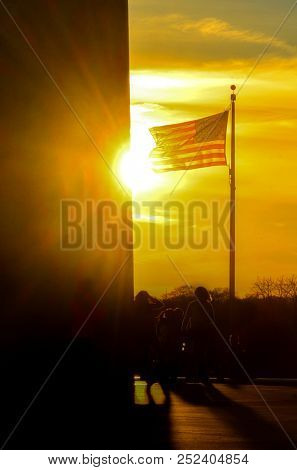Washington DC at sunset - Washington Monument and a waving National flag that circling the Monument - United States of America