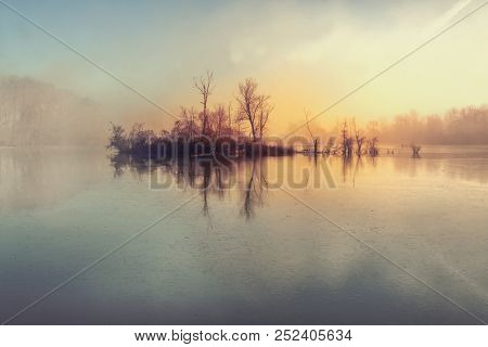 Island And Mysterious Fog Over River.morning Fog On A Lake.little Desert Island With Trees And Fog.