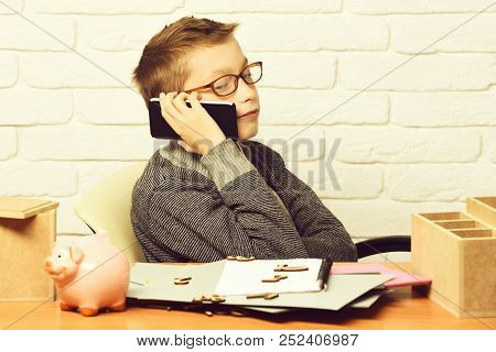 Holding And Speaking On Cell Phone On White Brick Wall Background, Copy Space. Young Cute Businessbo