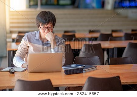 Young Asian Man With Eyeglasses Working With Laptop Computer Sitting In College Building. High Schoo