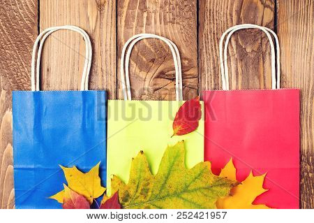Autumn Shopping. Fallen Leaves On Paper Bags. Flat Lay. Autumn Sales. Shopping Bags On Wooden Backgr