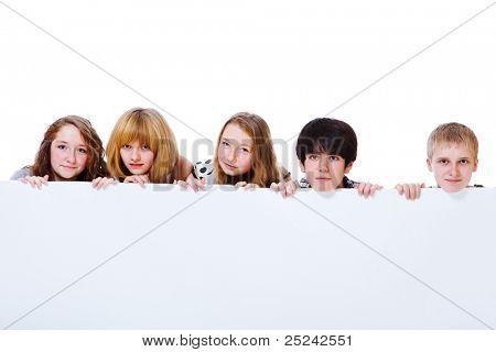 Teens group hiding behind large blank poster