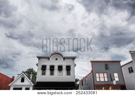 Downtown storefronts with storm clouds in the background