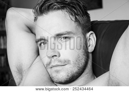 Hunky male shirtless man with pecs and muscles sitting on armchair looking at camera poster