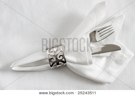 Silver cutlery with napkin ring and white linen napkin
