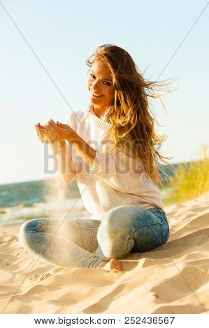 Joy And Carefree. Gorgeous Long Haired Woman Having Fun With Sand On Beach. Young Joyful Attractive