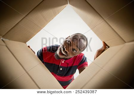 The Surprised Afrocan Man Unpacking, Opening Carton Box And Looking Inside. The Package, Delivery, S