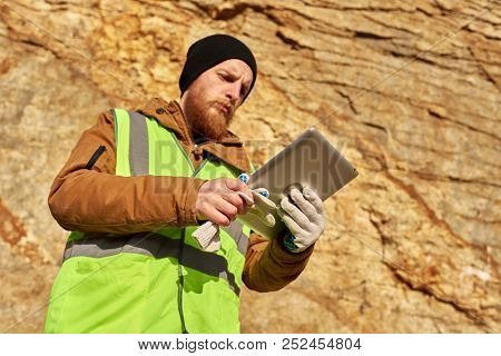 Low Angle  Portrait Of Bearded Industrial Worker Wearing Reflective Jacket Inspecting Mineral Mines