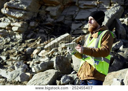 Side View  Portrait Of Young Industrial Worker Wearing Reflective Jacket Standing In Mineral Mines O