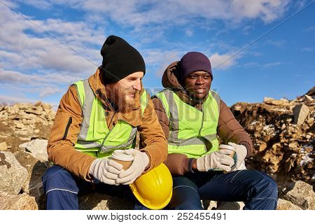 Portrait Of Two Industrial  Workers Wearing Reflective Jackets, One Of Them African, Relaxing Taking