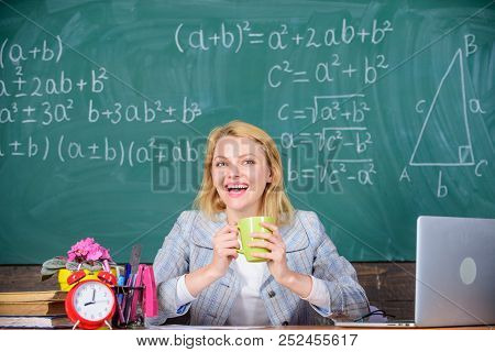 Pleasant relax after classes. Working conditions which prospective teachers must consider. Working conditions for teachers. Woman smiling teacher holds mug drink classroom chalkboard background poster