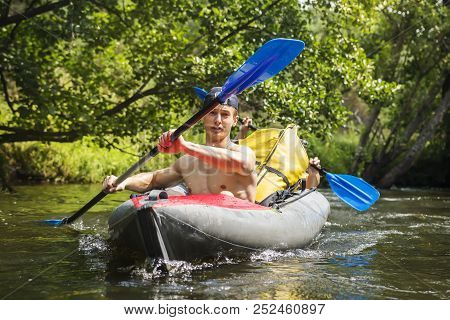 Kayaking On River. Athletic Guys In Canoe Rowing With Oars. Active Recreation In Nature. Water Adven