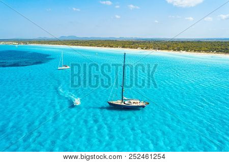 Yacht On The Azure Seashore In Balearic Islands. Aerial View Of Floating Sailboat And Motorboat In T